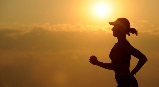 Kvinde som løber foran en solnedgang