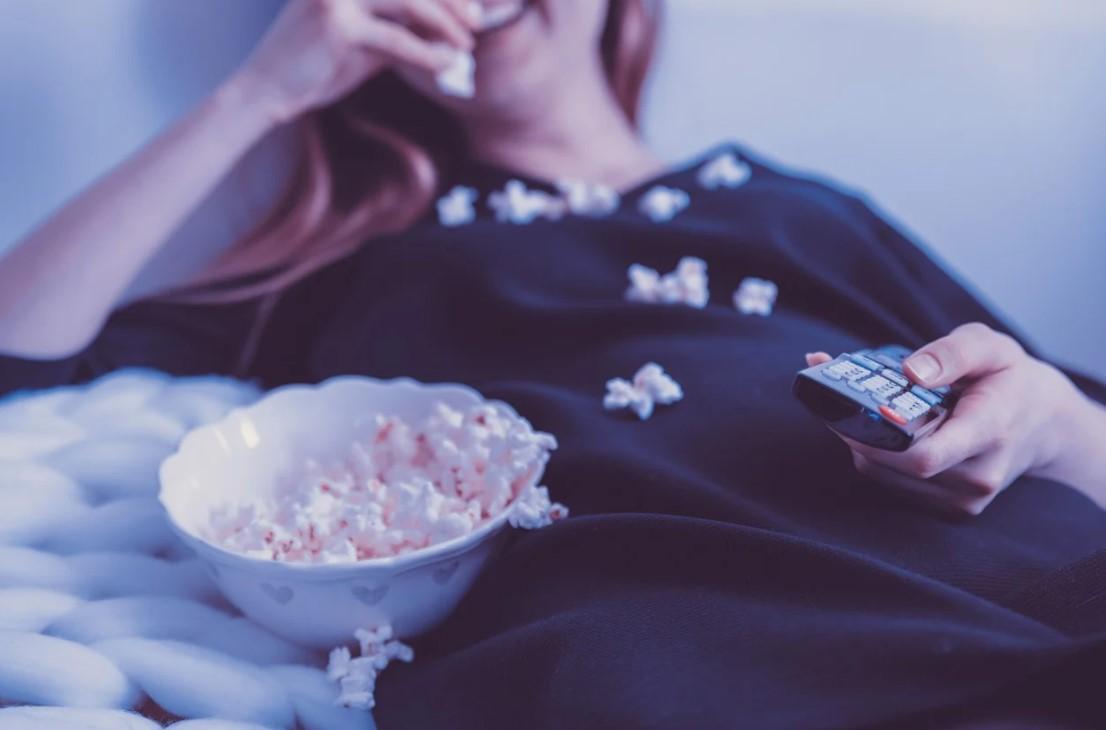 Kvinde med popcorn og fjernbetjening