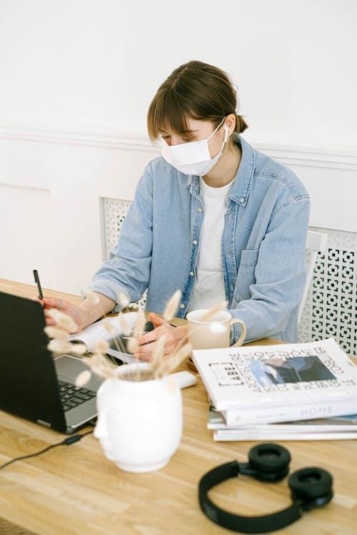kvinde med computer og mundbind